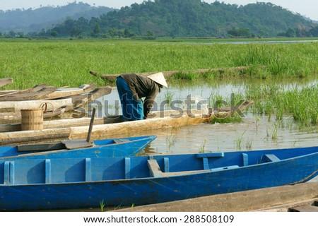 DAK LAK- VIET NAM- JUNE11: Group of Asian farmer go to work by row boat on Lak lake in summertime, family of ethnic minority, grass on lake, amazing view for Asia travel, Daklak, Vietnam, June11, 2015