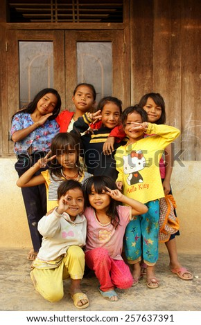 DAKLAK, VIET NAM- FEB 24: Group of unidentified Asian children standing, posing at wooden house of Vietnamese countryside, poor child, pretty girl happy and smiling, Dak Lak, Vietnam, Feb 24, 2015