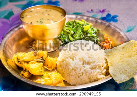 Dal Bhat, traditional Nepali meal platter with rice, lentils soup, vegetables, poppadum and spices. - stock photo