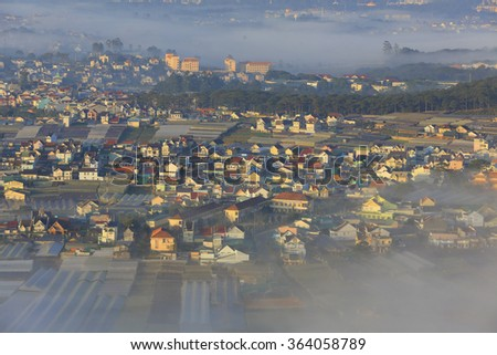Dalat city in Central highland of Vietnam on morning mist  - stock photo