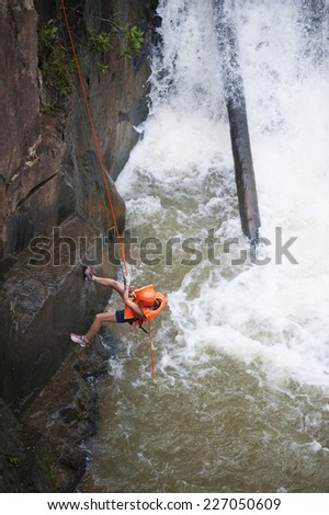 DALAT, VIETNAM - JULY 28, 2014: An unidentified Caucasian young woman tourist rappels in Datanla waterfall.