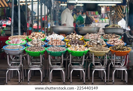 DALAT, VIETNAM - JULY 27, 2014: An unidentified man sells and cooks different kinds of seashells and seafood at a local food market. - stock photo