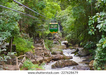 DALAT, VIETNAM - JULY 28, 2014: Unidentified tourists move in a cable car above Datanla waterfall. It is located 5 km away from the city center. - stock photo