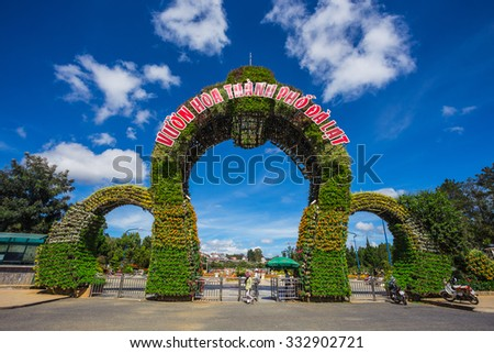 DALAT, VIETNAM - NOV 26, 2014: The main entrance of the Flower Park, one of major tourist attrations in the city. The arch consists of lots of flowers in pots settled on a metal frame. - stock photo