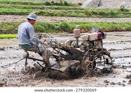 DALI - APRIL 25: Chinese farmer working on rice field on April 25, 2015 in Dali, China. Farmers in China have to work hard and earn average 1800 USD a year.  - stock photo