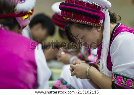 DALI, CHINA - MAY 16: A worker is using traditional method to process handmade silver craft in Dali, China on May 16 2014. Silver is a famous product in Dali, Yunan. - stock photo