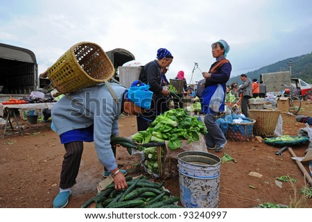 DALI, CHINA - MAY 22: Chinese farmers sell their goods on the market on May 22, 2010 in Dali, China. Many farmers depend on selling their products here and only make around $800 a year. - stock photo