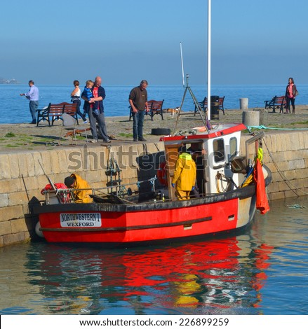 DALKEY, IRELAND - OCTOBER 12: The crew of a small, red trawler prepares to unload their catch at Bulloch Harbour on October 12, 2014 in Dalkey, Ireland.  - stock photo