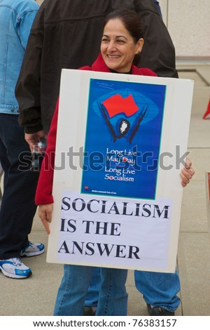 DALLAS - MAY 1: An unidentified woman holds a poster advocating socialism during a May Day protest on May 1, 2011 in Dallas, Texas. - stock photo