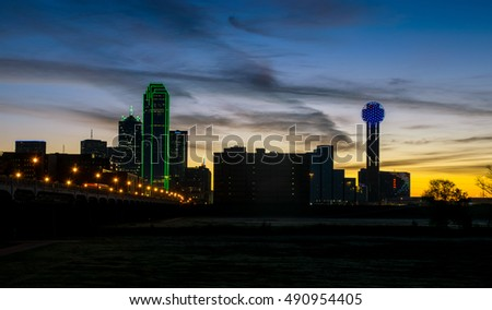 Dallas Texas at Night with Skyline Cityscape with Lights and Sunrise background with lights across the bridge spanning the Trinity Overlook Park