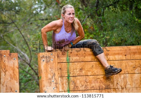 DALLAS, TEXAS - SEPTEMBER 15: Unidentified female participant climbs over a wooden wall obstacle in the Dash of the Titans Mud Run Race on September 15, 2012 in Dallas, Texas. - stock photo