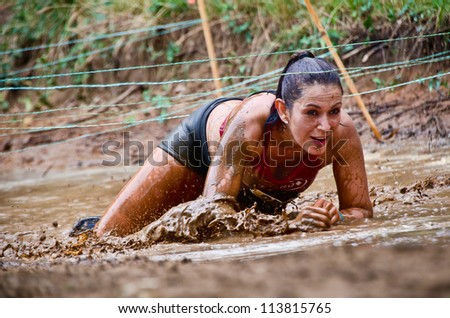 DALLAS, TEXAS - SEPTEMBER 15: Unidentified female participant crawls under the wires at a mud pit in the Dash of the Titans Mud Run Race on September 15, 2012 in Dallas, Texas. - stock photo