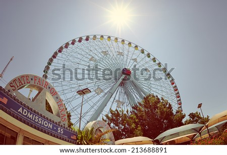 DALLAS, TX, - July 6, 2014: Texas Star, the largest ferris wheel in North America, rises above the horizon at Fair Park in Dallas, Texas. Fisheye capture with vintage filter effects.  - stock photo