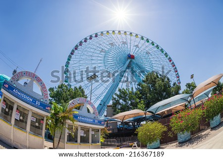 DALLAS, TX, - July 6, 2014: Texas Star, the largest ferris wheel in North America, rises above the horizon at Fair Park in Dallas, Texas. Fisheye capture.  - stock photo