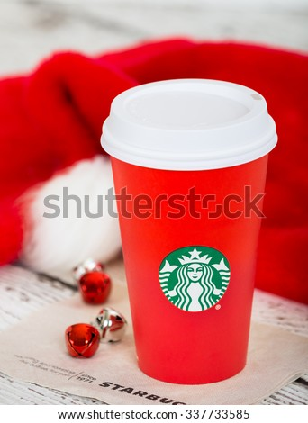 DALLAS, TX - NOVEMBER 10, 2015: A cup of Starbucks popular holiday beverage, served in the new 2015 designed red holiday cup. Displayed with Christmas hats and bells on white rustic table.  - stock photo
