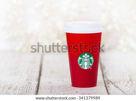 DALLAS, TX - NOVEMBER 19, 2015: A cup of Starbucks popular holiday beverage, served in the new 2015 designed red holiday cup. Displayed on white rustic table against holiday background. - stock photo