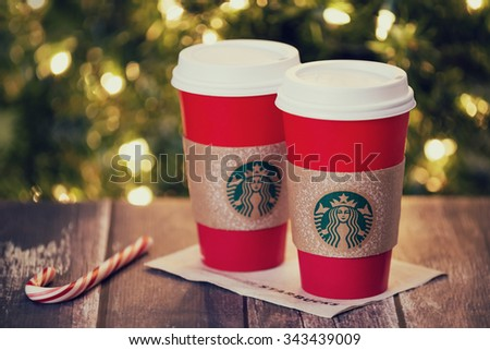 DALLAS, TX - NOVEMBER 24, 2015: A cup of Starbucks popular holiday beverage, served in the new 2015 designed red holiday cup. Displayed with a candy cane on rustic table against holiday background. - stock photo