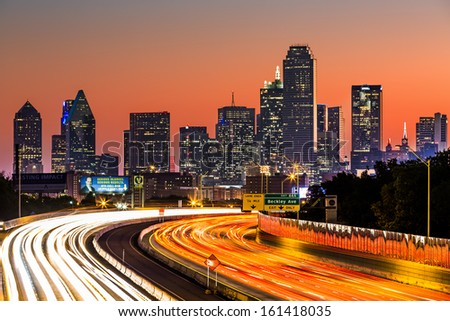 DALLAS, USA - OCTOBER 25: Dallas skyline at sunrise on October 25, 2013 in Dallas, USA. The rush hour traffic leaves light trails on I-30 (Tom Landry) freeway.
