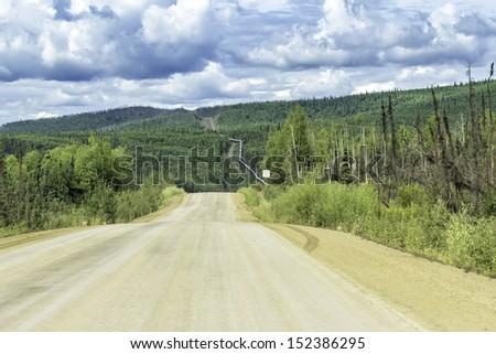 Dalton Highway and Trans-Alaska oil pipeline - stock photo