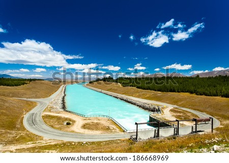 dam forming a crystal clear channel country's water for drinking and technical water needs. Background blue sky with clouds. In the background, mountains, forests and fields. New Zealand.