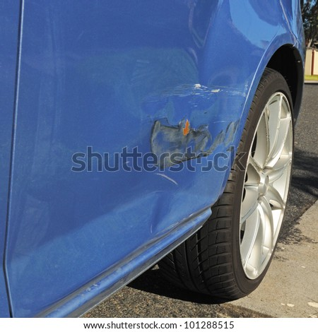 Damage on blue car door with bending, scratches and damaged paint after light road accident needs body repair, alloy wheel and asphalt in corner - stock photo