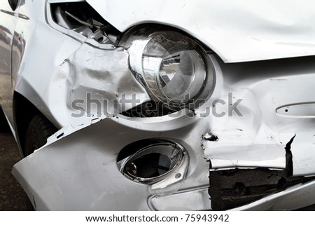 Damage to the front of a white car after an accident. - stock photo