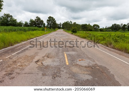 Damaged asphalt pavement road with potholes ,Asia - stock photo
