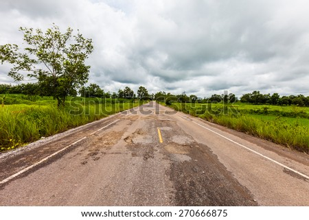 Damaged asphalt pavement road with potholes ,Asia - stock photo