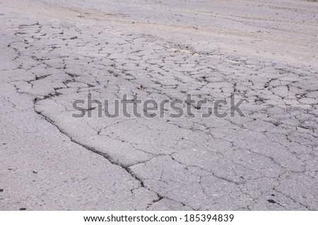 Damaged asphalt road, bad road - stock photo