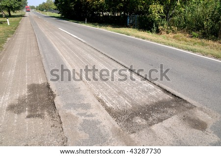 Damaged asphalt road prepared for reconstruction