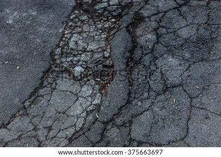 Damaged asphalt road with potholes caused by freeze-thaw cycles in winter. Bad road. Broken paving slabs on the sidewalk. Dangerous road. Emergency road. Injuries on the road