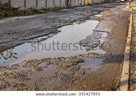 Damaged asphalt road with potholes caused by freezing and thawing cycles during the winter. Poor road. - stock photo