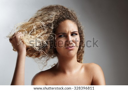 damaged blond hair concept. woman hold dry hair - stock photo