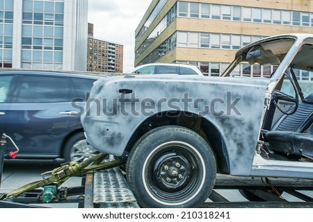 Damaged car on a tow truck after a street accident. - stock photo