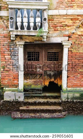 Damaged door and balcony at a Venetian canal. - stock photo