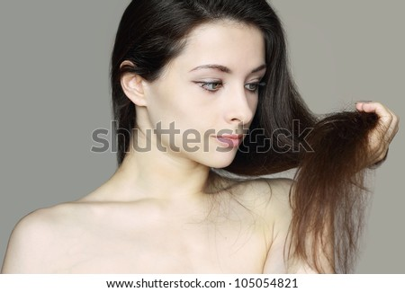 Damaged dry woman hair. Closeup portrait of woman holding hand long hair and thinking unhappy - stock photo