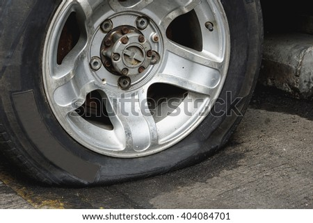 Damaged flat tire of an old car on the road