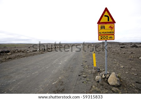 Damaged gravel road in Iceland and traffic sign - stock photo