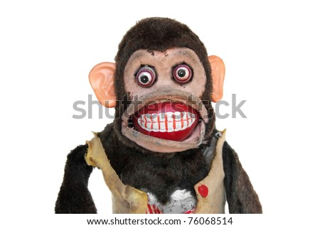 Damaged mechanical chimp with ripped vest, uneven eyes - stock photo