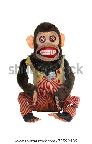 Damaged mechanical chimp with ripped vest, uneven eyes, missing cymbal