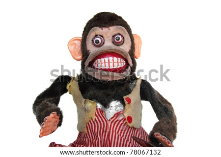 Damaged mechanical chimp with ripped vest, uneven eyes, missing cymbal - stock photo