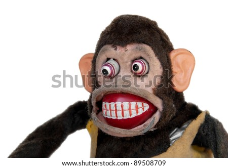 Damaged mechanical chimp with uneven eyes - stock photo