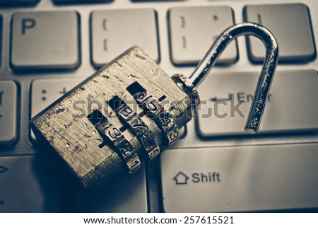 damaged metal security lock with password on computer keyboard - security concept in computer - stock photo
