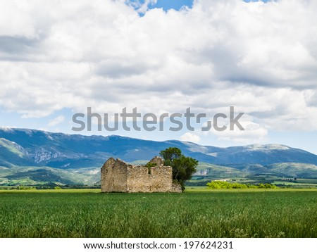 Damaged old stone barn on a corn field in France.