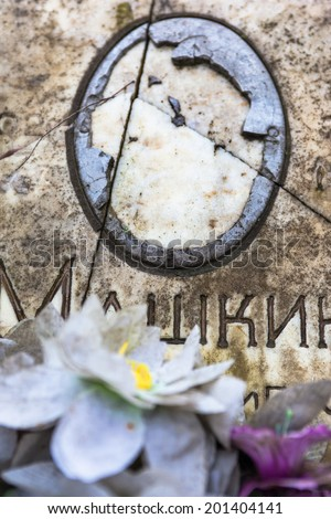 Damaged portrait of the buried person on the old gravestone. - stock photo