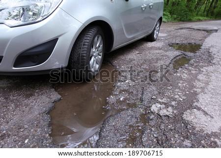 Damaged road full of cracked potholes in pavement - stock photo