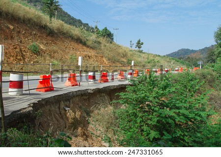 Damaged road in rural countyside - stock photo