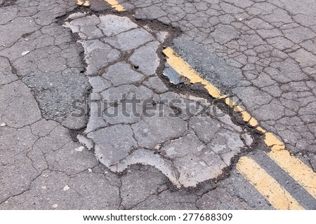 Damaged roadway of Yokohl Drive in California, USA - cracked asphalt blacktop with potholes and patches. - stock photo