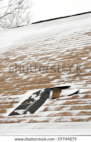 Damaged roof shingles blown off a home from a windy winter storm with strong winds. - stock photo