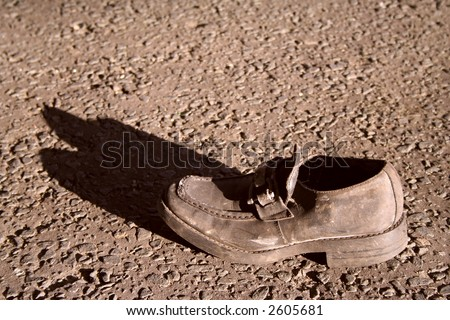 Damaged shoe left in street - stock photo